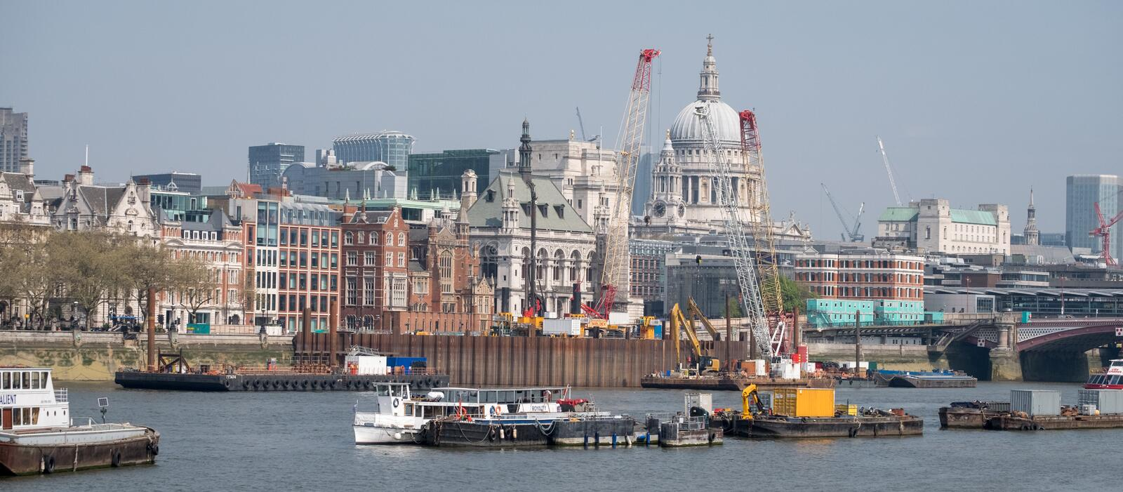 London UK. Panorama showing the iconic dome of St Paul`s Cathedral, the River Thames, cranes and buildings under construction royalty free stock photos