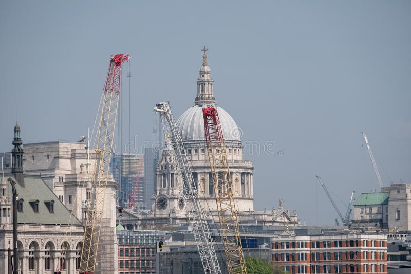 London UK. Panoramic view of the iconic dome of St Paul`s Cathedral, the River Thames, cranes and buildings under construction royalty free stock images