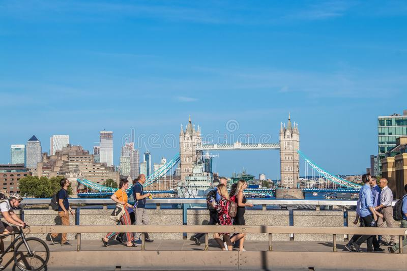 Pedestrians crossing London Bridge with Tower Bridge raised for ship to pass under in the background - some. 2019_07_24_London UK Pedestrians crossing London royalty free stock images