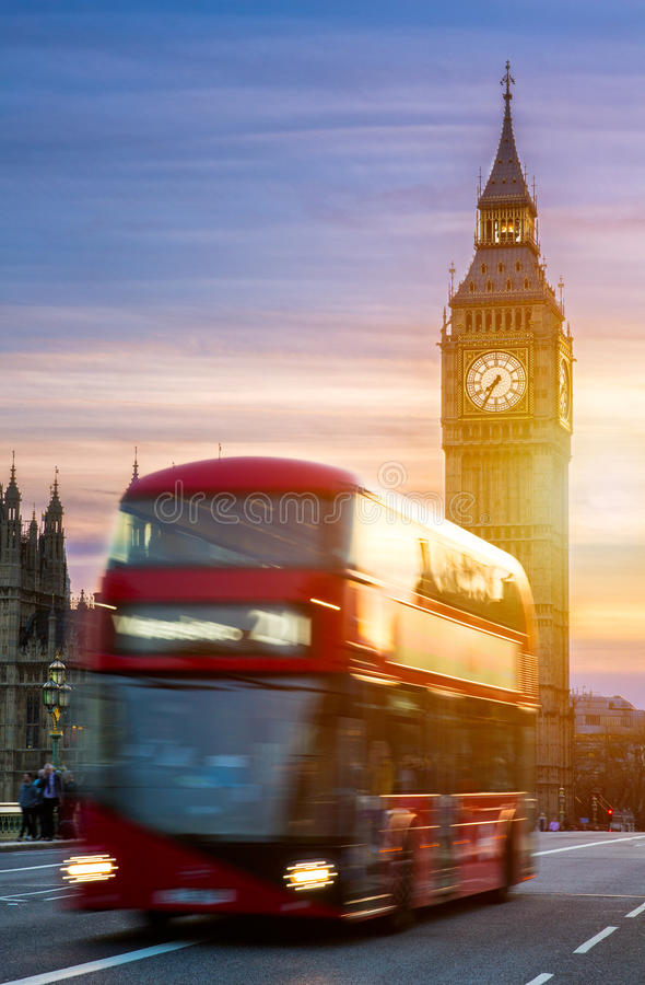 London, the UK. Red bus in motion and Big Ben, the Palace of Westminster. The icons of England stock photo