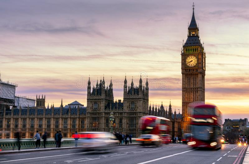 London, the UK. Red bus in motion and Big Ben, the Palace of Westminster. The icons of England royalty free stock images