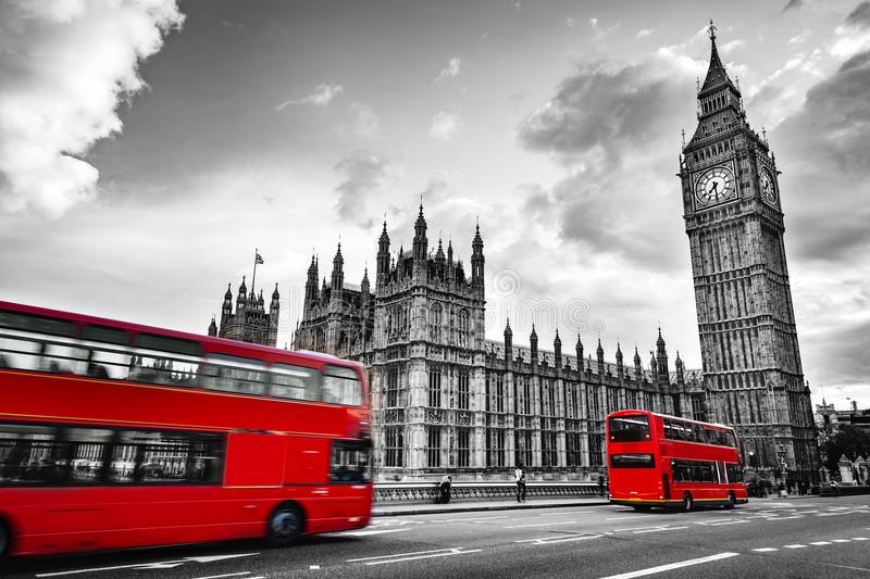 London, the UK. Red buses in motion and Big Ben. The Palace of Westminster. The icons of England in vintage, retro style. Red in black and white stock photography