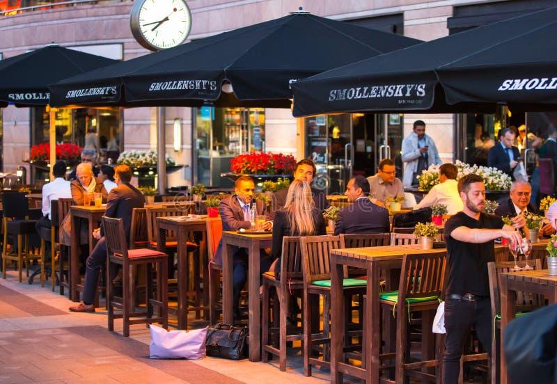 LONDON UK - 7 SEPTEMBER, 2015: Canary Wharf uteliv Folk som sitter i lokal restaurang efter lång tidarbetsdags arkivfoton