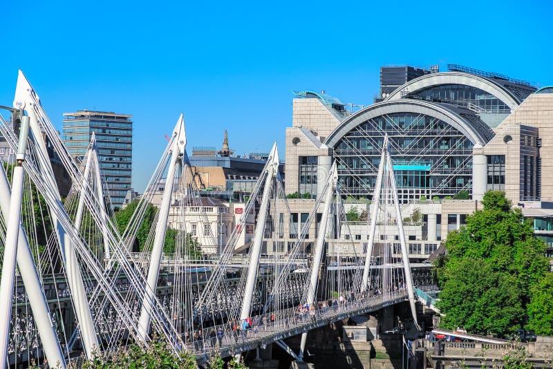 London UK - September 22, 18 - Hungerford bro och femtioårsjubileumbroar med flodsidan av den Charing Cross stationen i arkivfoton