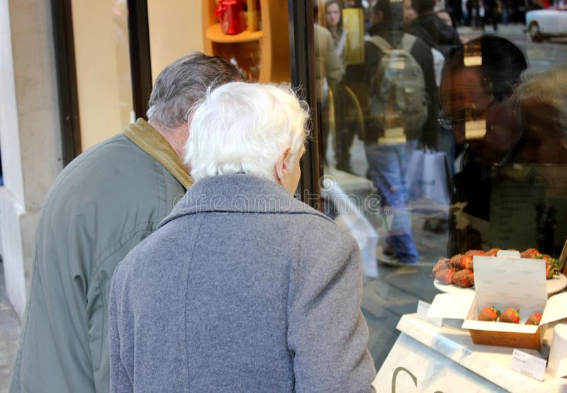 Elderly couple looking at delicious chocolates through a shop window stock image