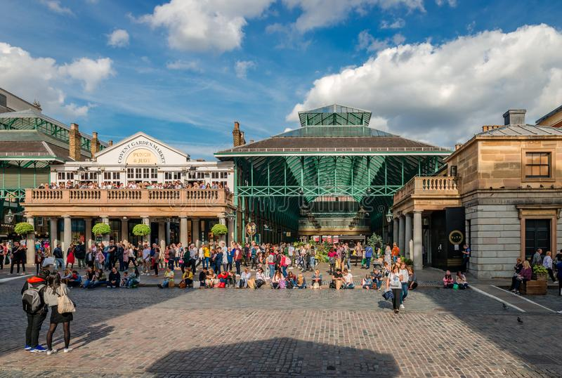 Tourists at Covent Garden Piazza. London / UK - September 15 2018: Tourists enjoy a sunny afternoon at the central square in Covent Garden, aka Covent Garden royalty free stock images