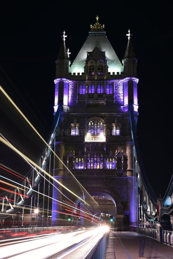 London, UK, tornbron på natten med ljusa slingor av bussar och bilar på bron, lång exponering sköt i lågt ljus royaltyfri foto