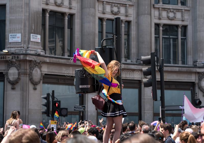 Woman climbs up traffic light pole at Oxford Circus, London, to get a better view of the Gay Pride Parade. London UK. Woman with LGBT rainbow flag climbs up the stock photos