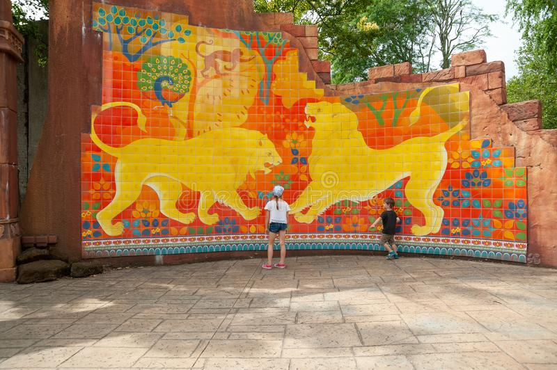 London, UK. 08-03-2019. ZSL London Zoo. Colourful tiled wall depicting ancient tale about two fighting male lions. stock photo
