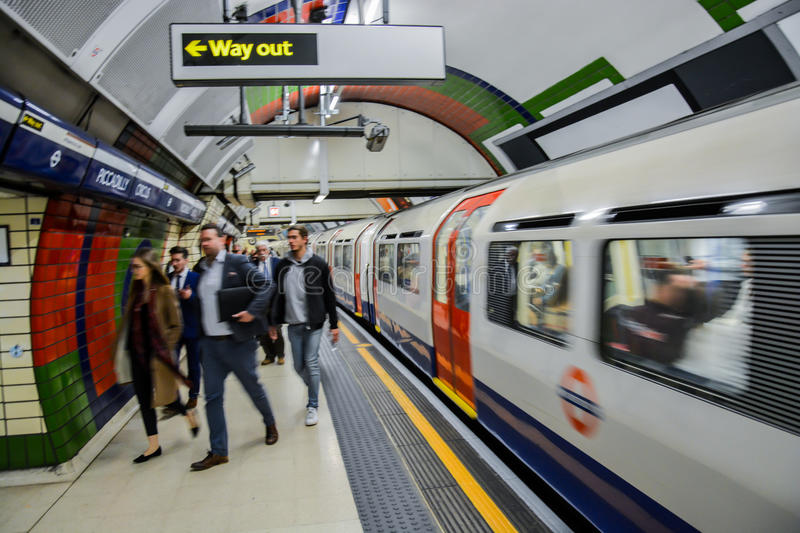 London Underground - rush hour. A picture of commuters rushing to get to work in the morning at Piccadilly tube station as the train pulls out at speed royalty free stock image