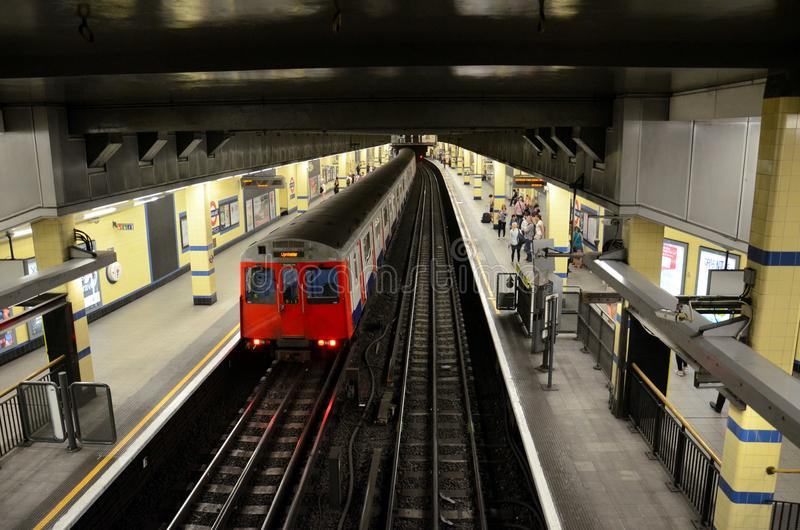 London Underground tube subway train leaves station platform. London, England - June 8, 2014: A District Line subway train leaves Aldgate East station platform royalty free stock photos