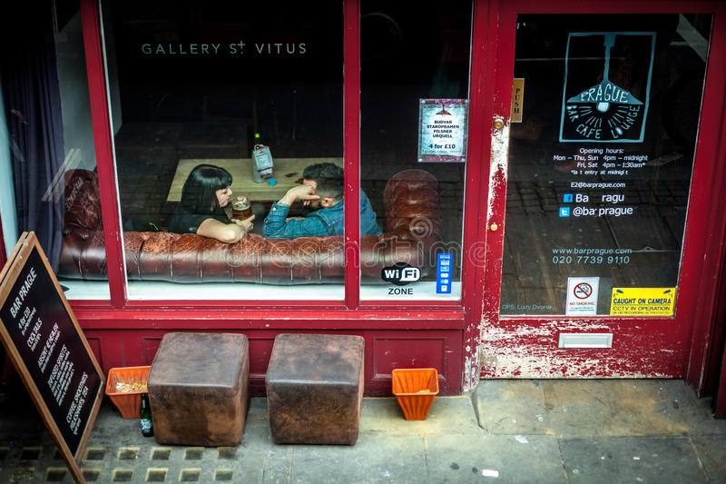 London, United Kingdom - April 5, 2015. Kingsland Rd. Couple chatting over a beer on a Chesterfield sofa. London, United Kingdom - April 5, 2015. Kingsland Rd royalty free stock photo