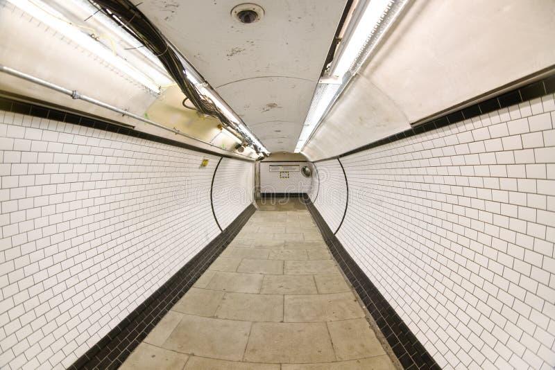 London, United Kingdom - February 24, 2007: Extreme wide angle fisheye photo of tunnel at London tube station leading to train stock images