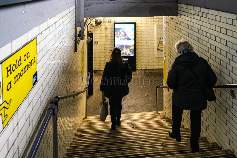 London, United Kingdom - February 01, 2019: Passengers walking down the stairs at pedestrian subway leading to other platform at stock photo