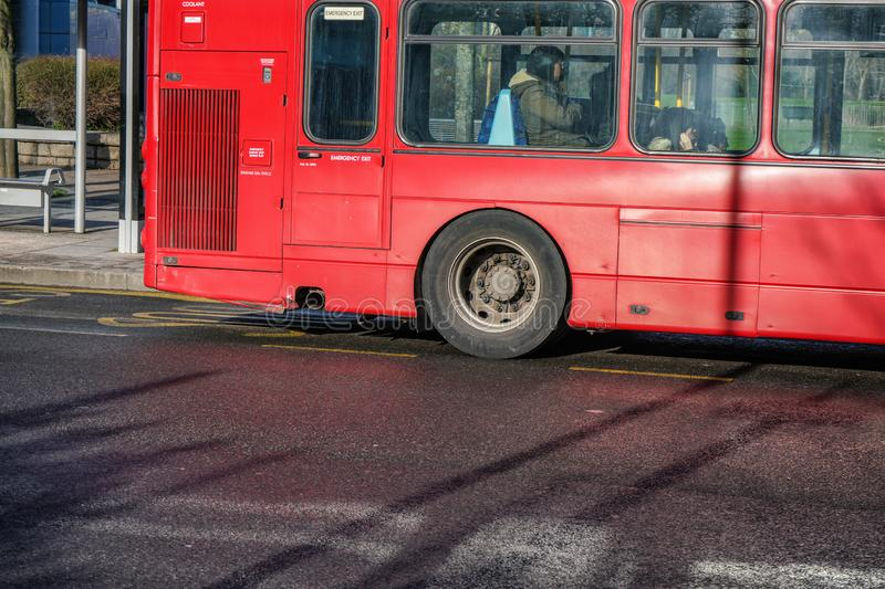 London, United Kingdom - February 03, 2019: Rear detail of iconic red bus used in UK capital, with passengers commuting in the stock images