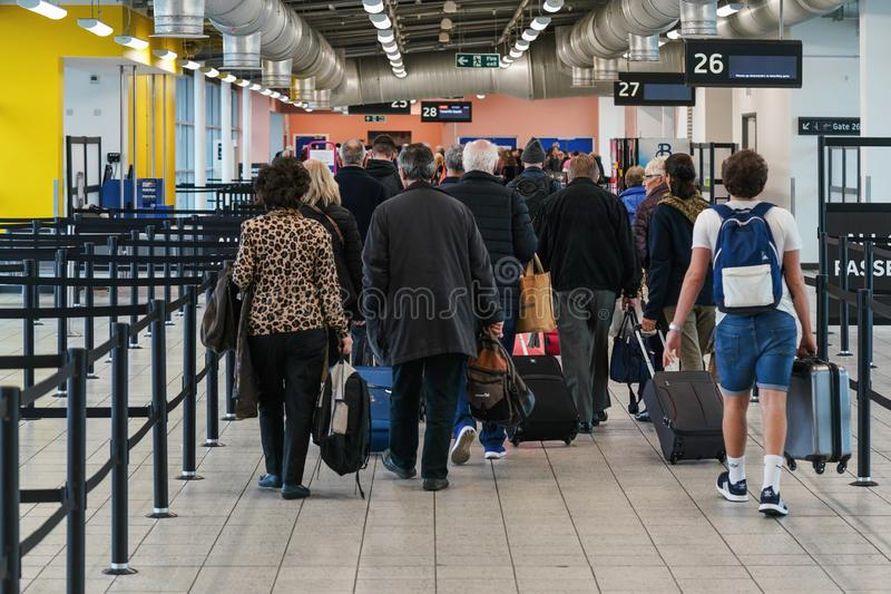 London, United Kingdom - February 05, 2019: View from back to group of passengers walking to the gate before boarding the airplane royalty free stock image