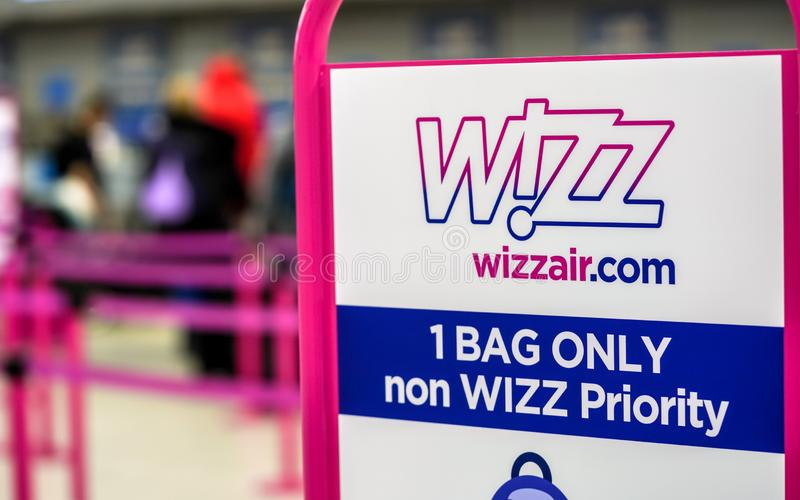 London, United Kingdom - February 05, 2019: Wizzair info table about maximum baggage size, blurred people at check in desks in royalty free stock photo