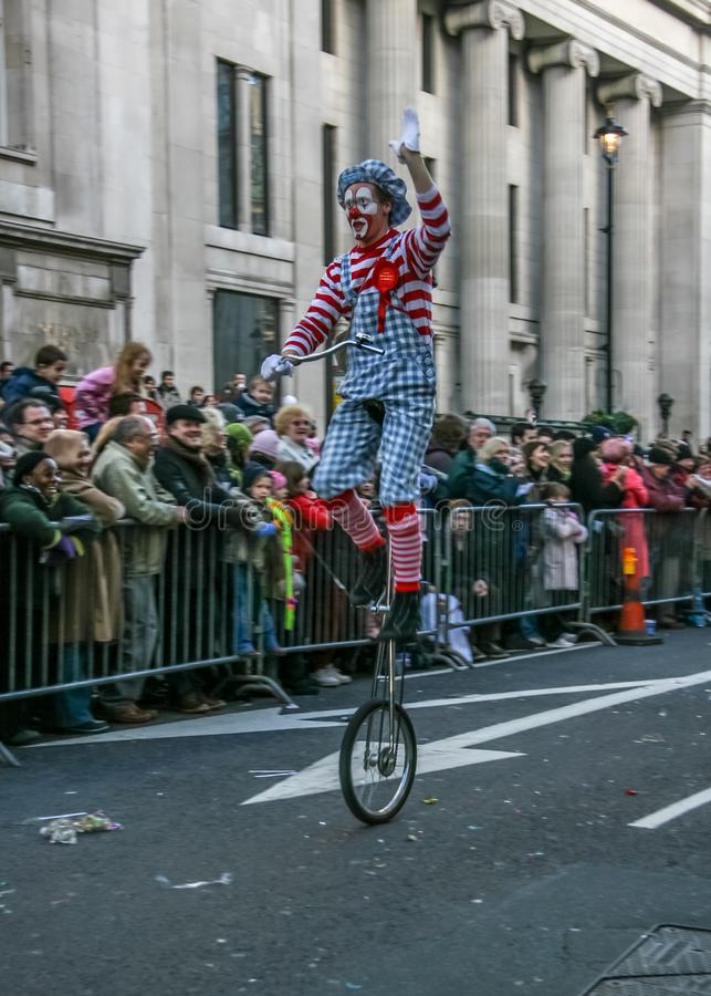 London, United Kingdom - January 1, 2007: Man in clown costume rides unicycle, and waves to cheering crowd, during New Year`s Day stock photo