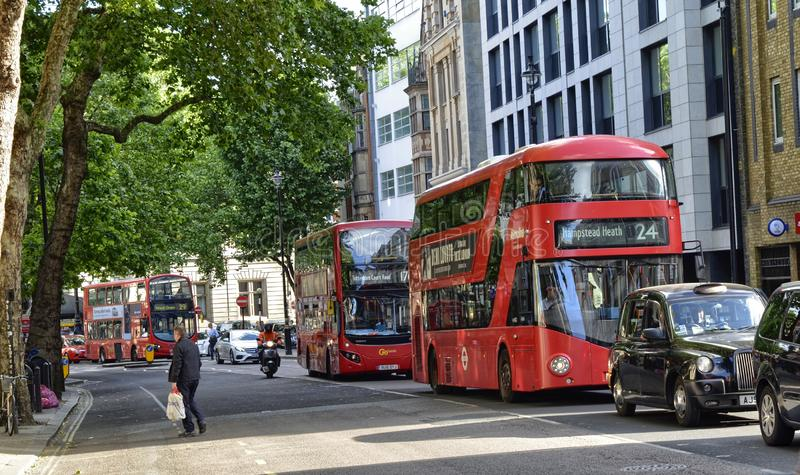 London, United Kingdom, June 2018. The appearance of the city around the Leicester square metro station. Double-decker buses, taxis called cabs, crowds of royalty free stock photos