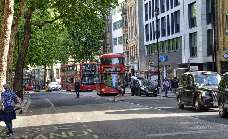 London, United Kingdom, June 2018. The appearance of the city around the Leicester square metro station. Double-decker buses, taxis called cabs, crowds of royalty free stock photography