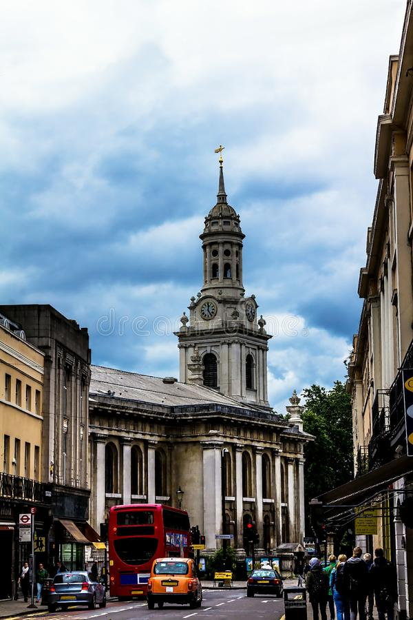 Clock tower of St Alfege Parish church, Royal Borough of Greenwich in London behind a common houses. London, United Kingdom - June 09, 2015: Clock tower of stock photography