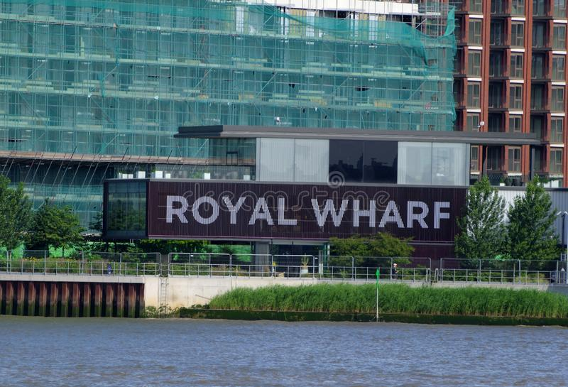 Riverside sign for Royal Wharf housing redevelopment adjacent to River Thames. London, United Kingdom - June 23, 2018: Riverside sign for Royal Wharf housing royalty free stock photos