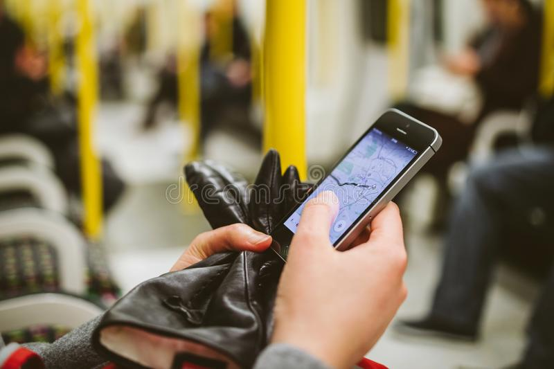 Woman insde metro train tube wagon using smartphone to see the m. LONDON, UNITED KINGDOM - MAR 10, 2015: Woman using smartphone telephone inside metro tube stock photos