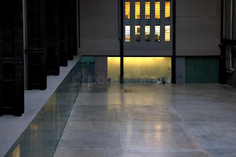 London, United Kingdom - March 17, 2007: Unknown couple sitting on floor of Tate modern main hall. Art gallery is situated inside royalty free stock photos