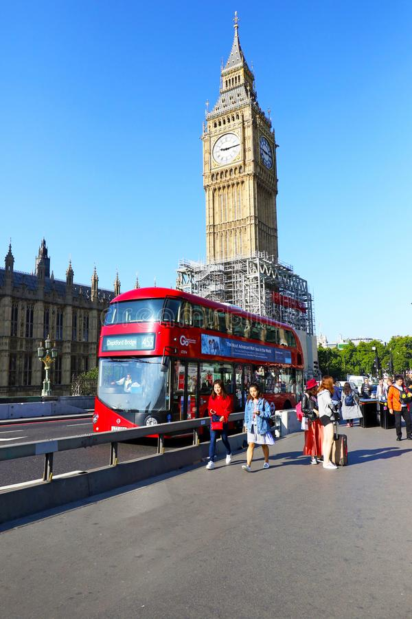 LONDON, United Kingdom - Sep 1, 2017: Tourist walking near Big Ben. Red double decker bus driving by. royalty free stock photo