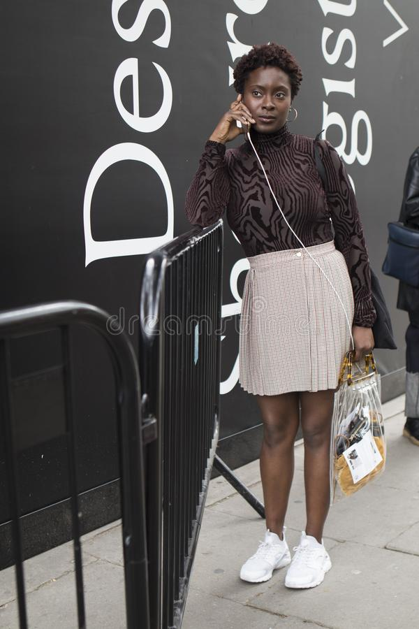 People on the street during the London Fashion Week. Short-haired girl in a short skirt stock image