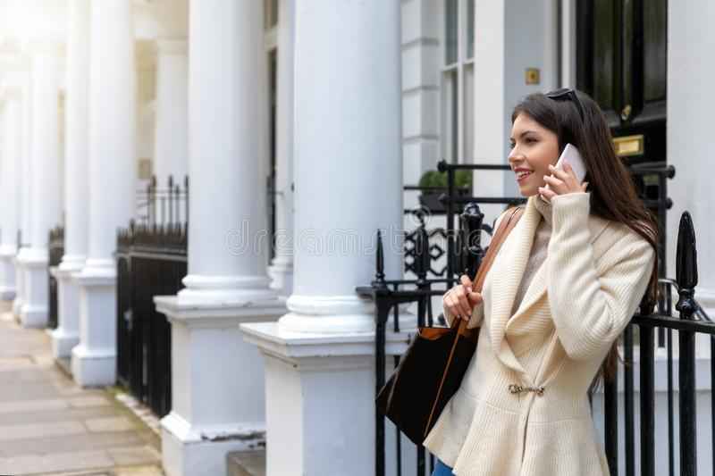 London woman talks on her in front of traditional Victorian Houses. A beautiful fashionista London woman talks on her mobile phone whilst waiting on a street in stock photo