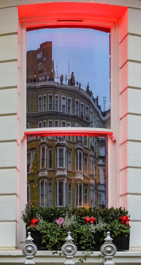 London - Yellow building with bay windows reflected in a window across the street with dramatic red lighting on sills and a window. London - A Yellow building royalty free stock image
