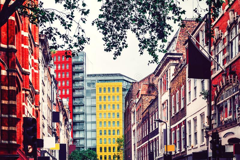 London. Yellow high apartment block surrounded by red brick traditional english houses. stock photos