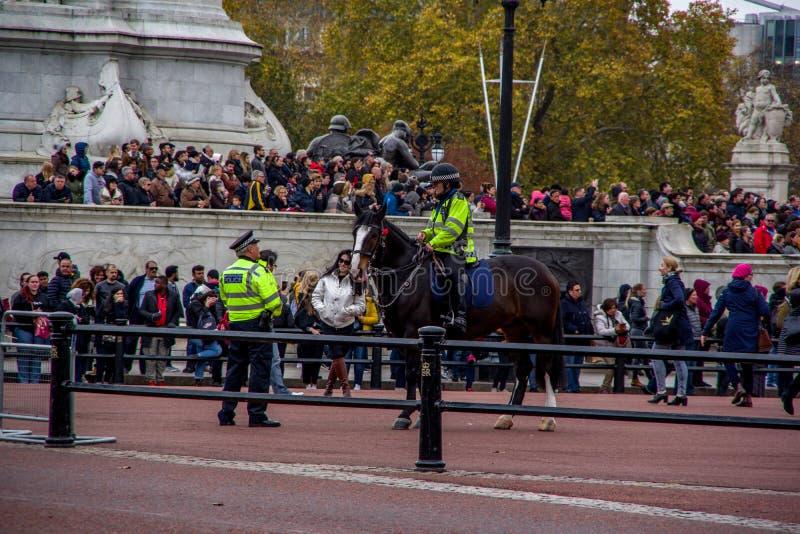 LONDRA, INGHILTERRA - 9 NOVEMBRE 2018: Poliziotto sul cavallo discutere con l'altro poliziotto su terra Cerimonia di Buckingham P immagini stock libere da diritti