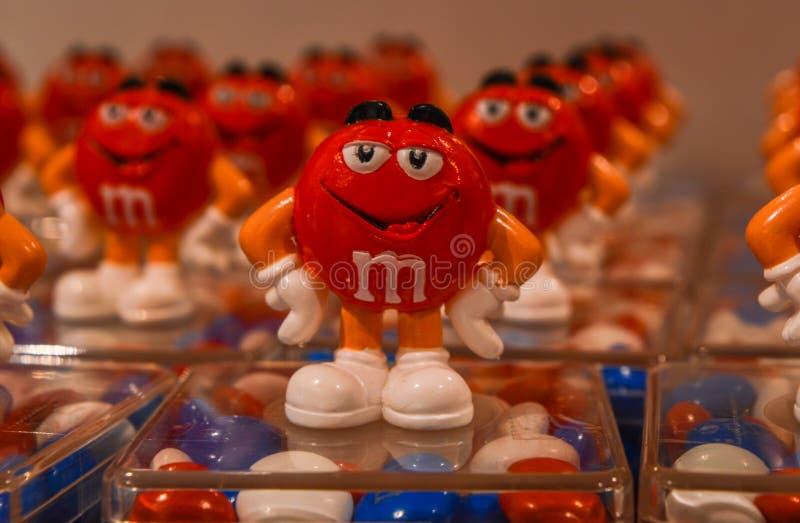 Londra, Regno Unito - 7 agosto 2018: Caramelle di cioccolato variopinte del ` s di M&M in recipienti di plastica, con la mascotte fotografia stock