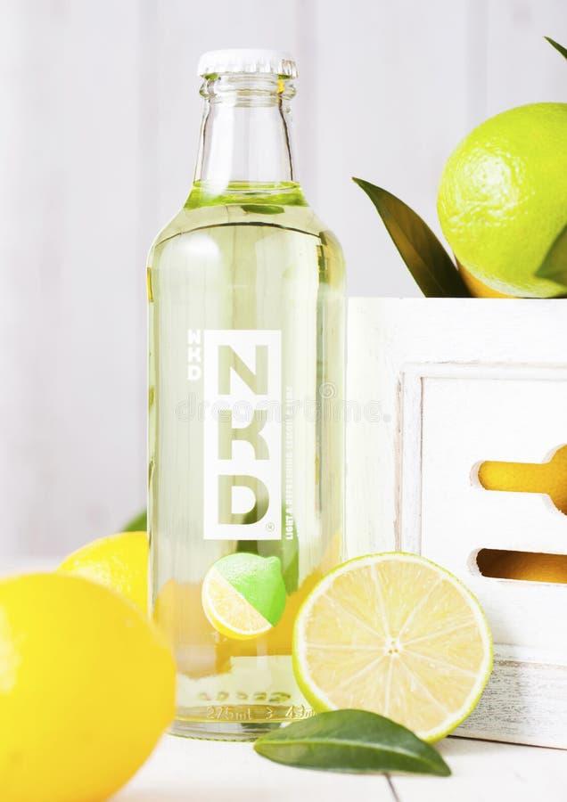 LONDRA, REGNO UNITO - 27 APRILE 2018: Bottiglia di vetro della bevanda alcolica del cocktail di NKD su fondo di legno con i limon fotografia stock libera da diritti