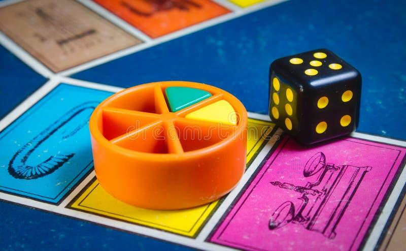 Londra, Regno Unito - 7 aprile 2019: Il primo piano del gioco da tavolo classico Trivial Pursuit con il nero muore e pezzi di pla fotografie stock libere da diritti