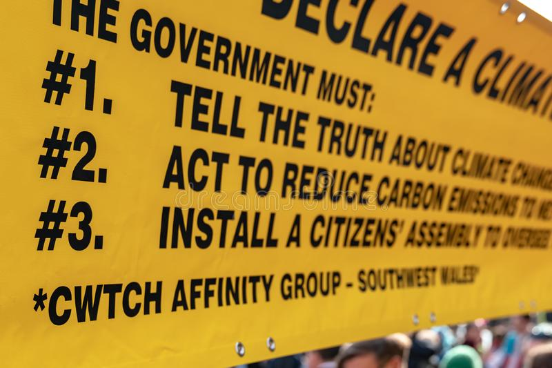 Londra, Regno Unito - 15 aprile 2019: Un'insegna gialla dei sostenitori di ribellione di estinzione di tre richieste del centro d immagine stock libera da diritti