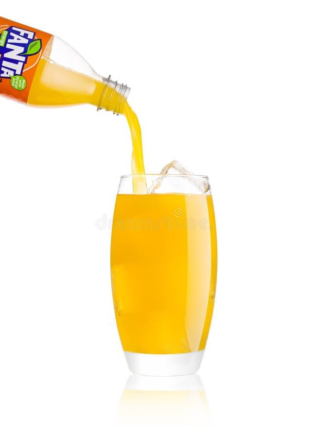 LONDRA, REGNO UNITO - 2 GENNAIO 2018: Bibita di versamento di Fanta dalla bottiglia a vetro su bianco Fanta è popolare frutta-con immagine stock