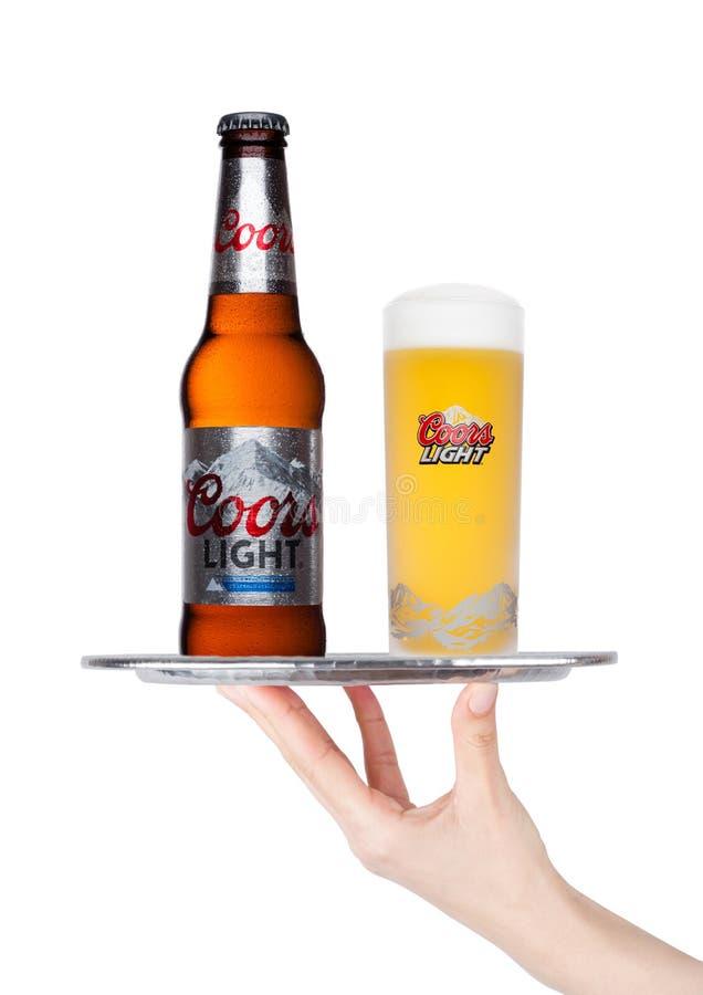 LONDRA, REGNO UNITO - 24 GENNAIO 2018: La mano tiene il vassoio con la bottiglia di birra ed il vetro di Coors su bianco immagine stock