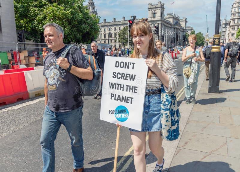 Londra/Regno Unito - 26 giugno 2019 - giovane donna porta un segno del mutamento climatico fuori del Parlamento fotografia stock libera da diritti