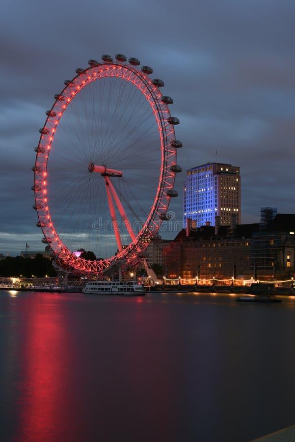 Londra Regno Unito: 26 giugno 2015, occhio maestoso di Londra e costruzioni iconiche di Londra alla notte sulla banca del Tamigi fotografie stock libere da diritti