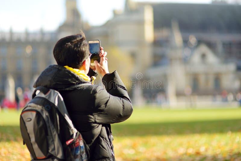 LONDRA, REGNO UNITO - 19 NOVEMBRE 2017: Giovane turista maschio che prende una foto con il suo telefono cellulare Bello giorno di fotografia stock libera da diritti