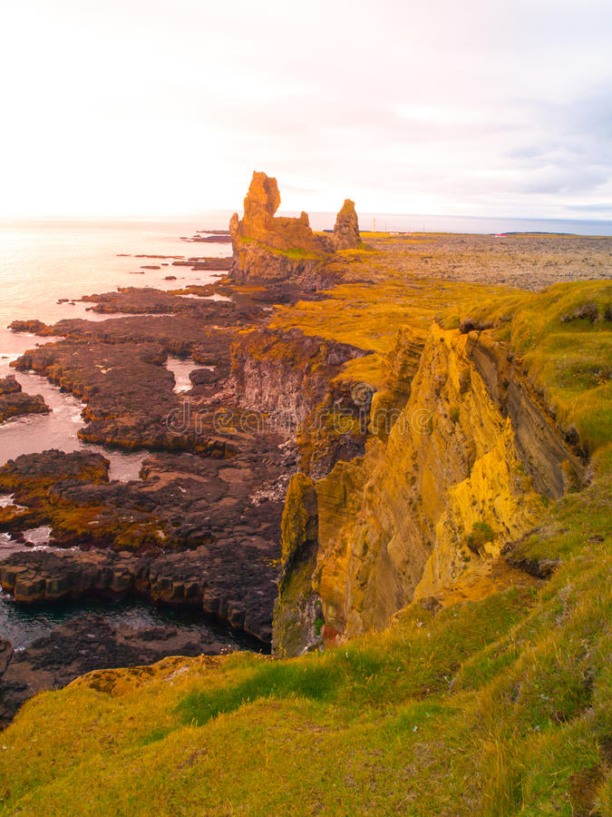 Londrangar, rock lava formation in the sea. Eroded basalt cliffs in the wild sea at coastline on Sneafellsnes peninsula royalty free stock image