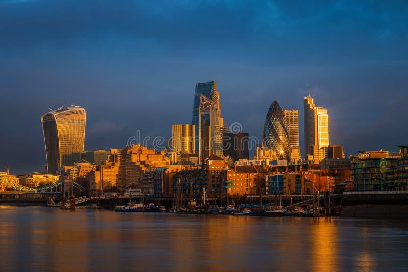 Londres, Angleterre - ciel dramatique étonnant et lumière du soleil d'or d'heure au secteur de banque de Londres photographie stock