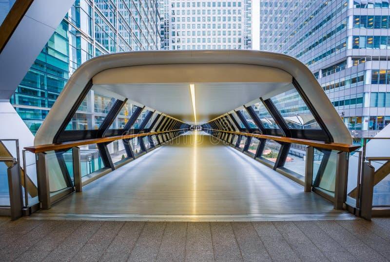 Londres, Angleterre - passerelle piétonnière de rail croisé au secteur financier de Canary Wharf avec des gratte-ciel image stock