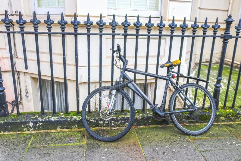 Londres - bicicleta velha que se inclina contra a construção exterior da cerca do ferro forjado com janela de baía bem no fundo - imagem de stock