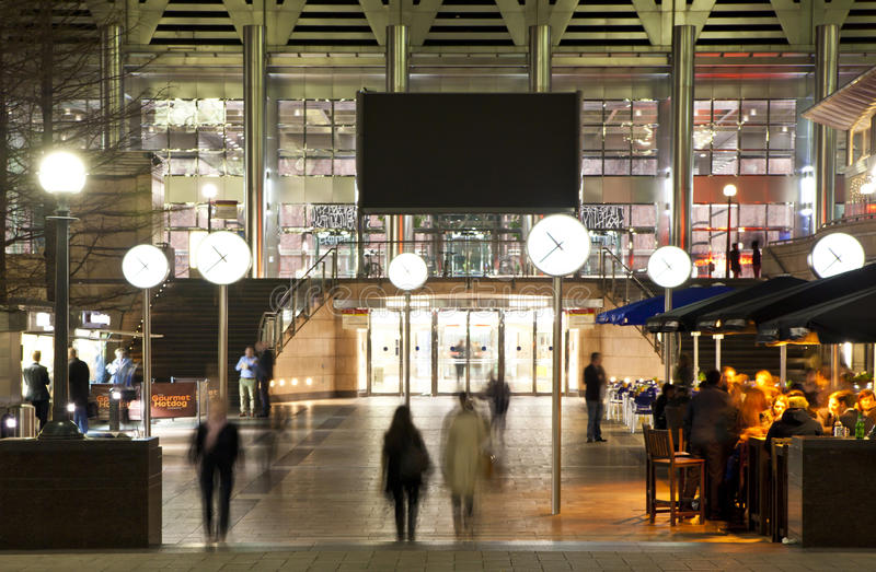 LONDRES, CANARY WHARF Reino Unido - 4 de abril de 2014 la opinión cuadrada de Canary Wharf en noche se enciende con los oficinista imagenes de archivo