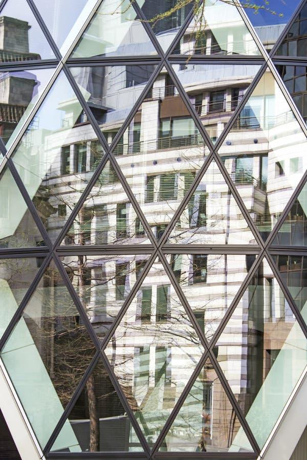 Londres, distrito financiero, reflexión de un edificio en el pepinillo imagenes de archivo