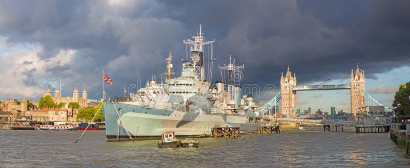 Londres - el panorama del puente y del crucero Belfast de la torre en luz de la tarde con las nubes de tormenta dramáticas imagen de archivo libre de regalías